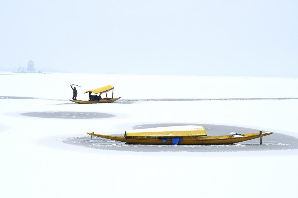 Un barquero dirige su bote en el lago Dal parcialmente congelado después de una nevada en Srinagar.