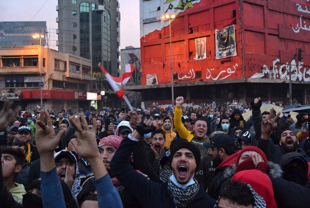 Protestantes libaneses gritan slogans mientras se reunen en la plaza al-Nour