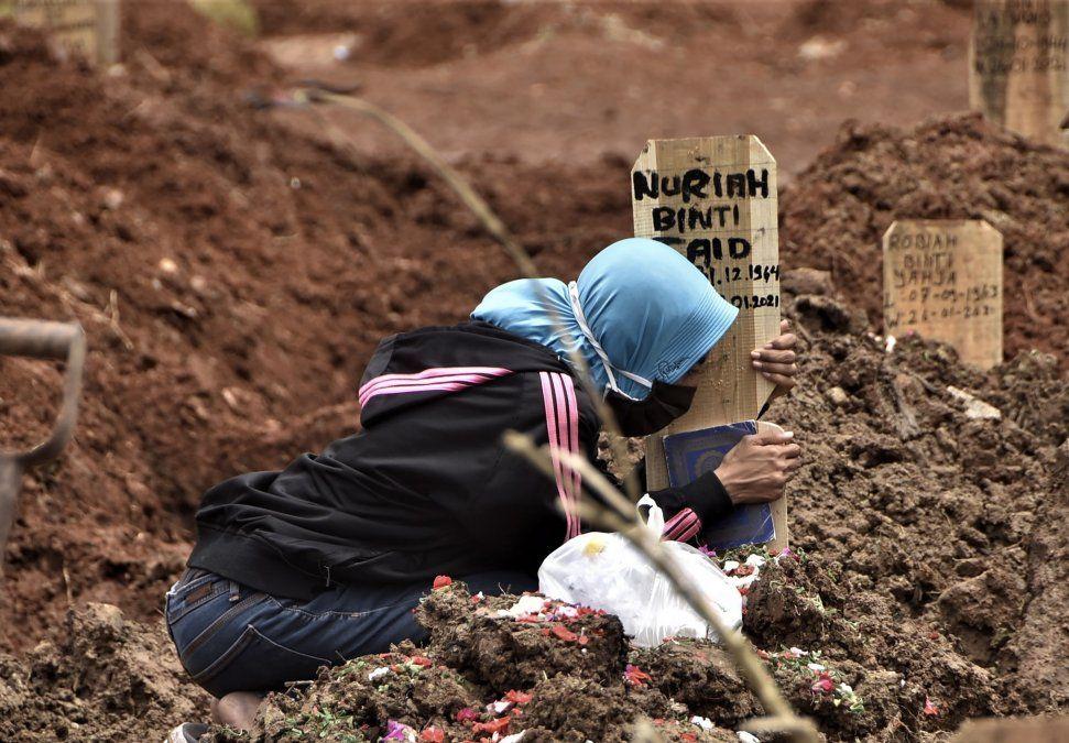 Una mujer se aferra a la tumba de un ser querido que murió por Covid en el cementerio de Bekasi