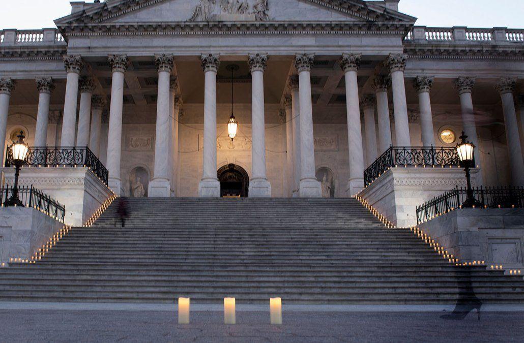 La gente pasa junto a velas eléctricas antes de una ceremonia en el Capitolio en honor a las 500.000 personas que perdieron la vida en Covid-19