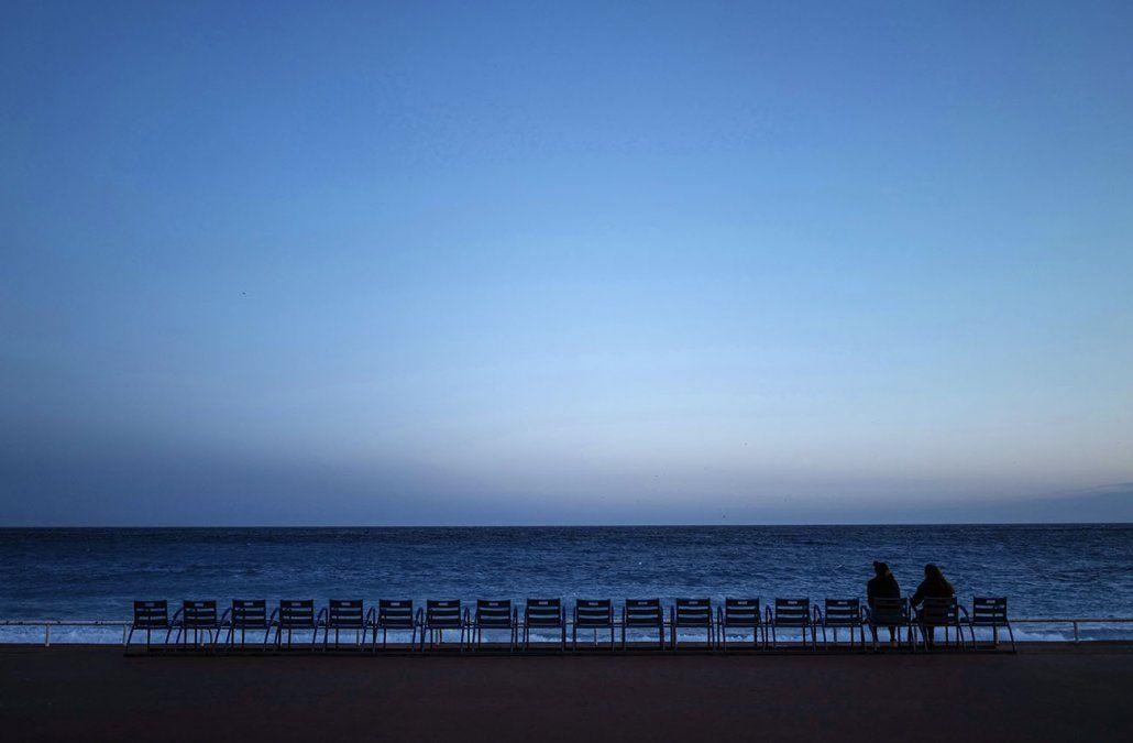 Dos personas se sientan frente al mar Mediterráneo en el Promenade des Anglais en la ciudad de Niza. El ministro de salud francés dijo que el 20 de febrero de 2021