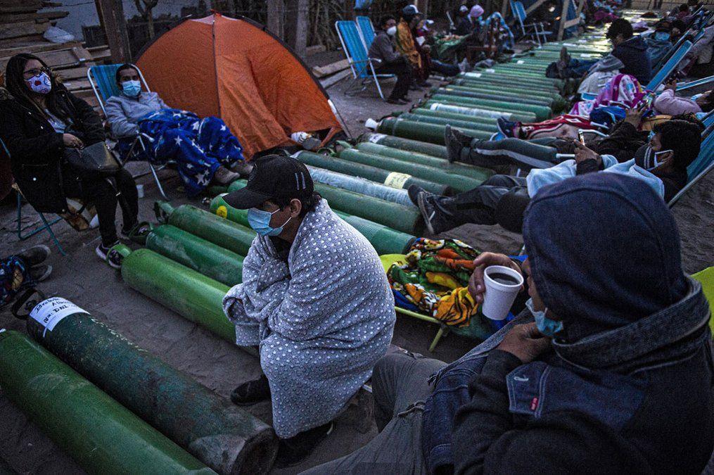 Personas acampan mientras esperan para rellenar cilindros de oxígeno vacíos en Villa El Salvador