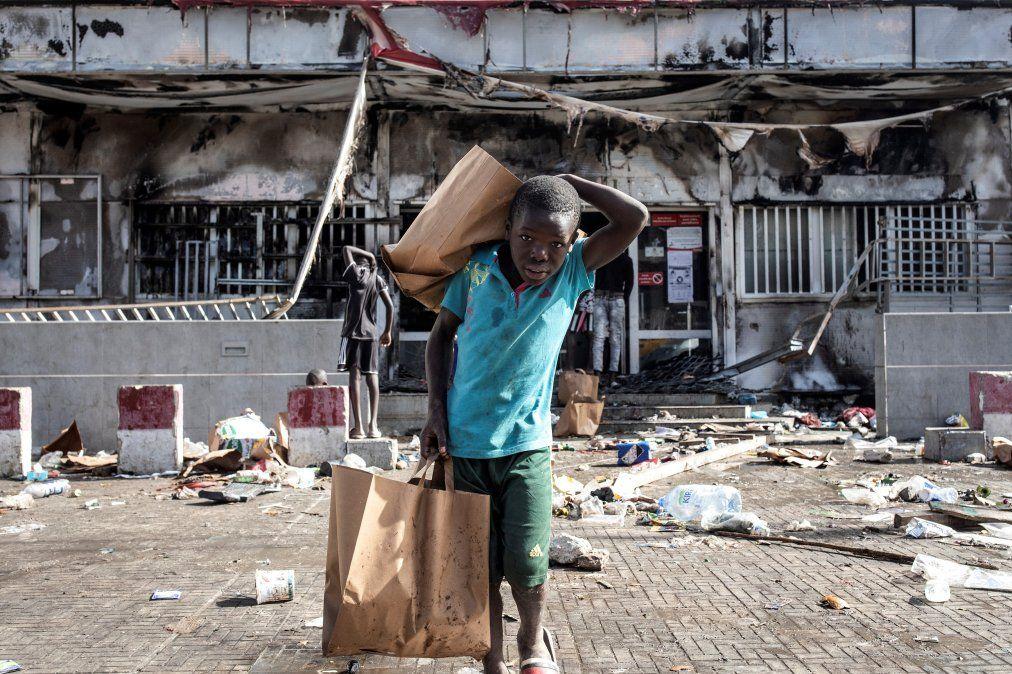 Un niño sostiene bolsas de la compra mientras se aleja de un supermercado Auchan incendiado y saqueado en Dakar