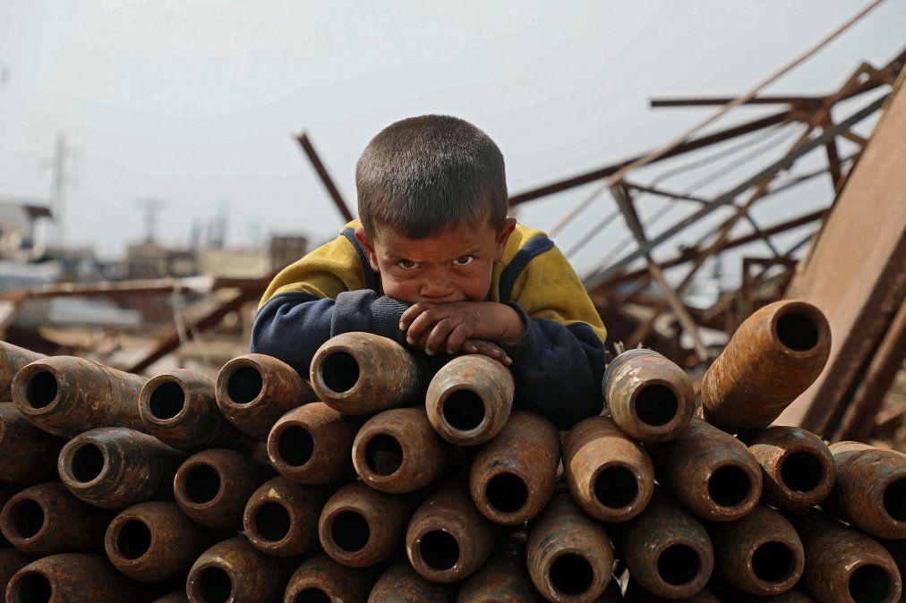 Un niño sirio posa encima de una pila de proyectiles neutralizados en un depósito de chatarra de metal en Siria.