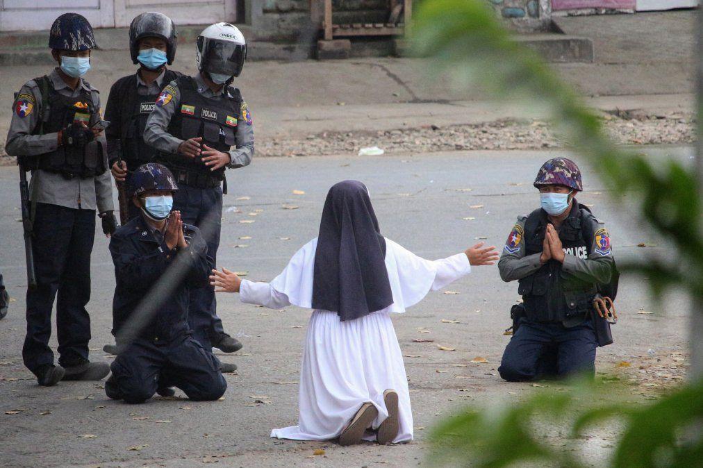 Una foto del Myitkyina News Journal muestra a una monja que suplica a la policía que no dañe a los manifestantes en Myitkyina