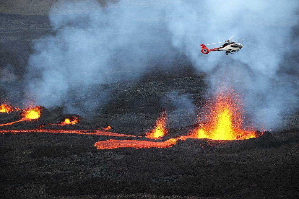 Una imagen de un helicóptero volando miestras la lava entra en erupción en el volcán Piton de la Fournaise.