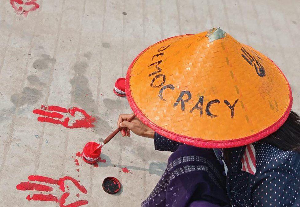 Un manifestante pintando los símbolos de los tres saludos con los dedos en el suelo como parte de una manifestación de huelga sangrante.