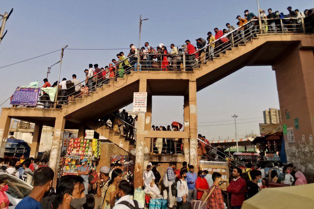 La gente se aglomera en una estación de autobuses para llegar a sus lugares de origen horas antes de que entre en vigor en Nueva Delhi un cierre de una semana ordenado por el gobierno de Delhi.
