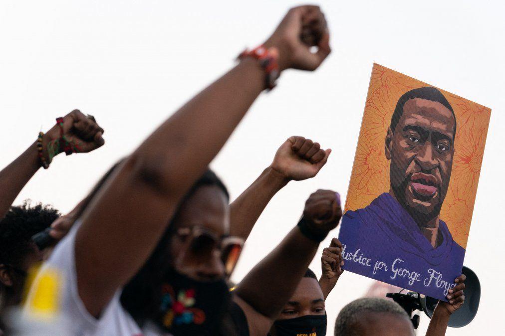 La gente levanta los puños y sostiene un retrato de George Floyd durante una manifestación tras el veredicto de culpabilidad en el juicio de Derek Chauvin el 20 de abril de 2021 en Atlanta