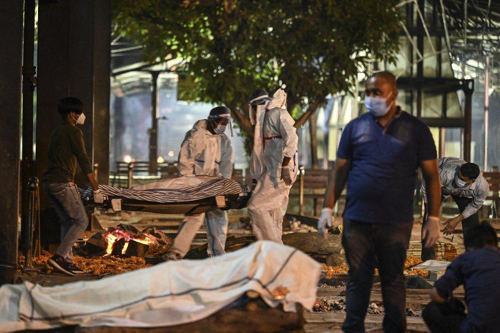 Familiares y personal llevan el cadáver de una víctima del Covid-19 en el crematorio Nigambodh Ghat
