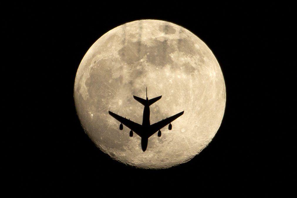 Se muestra un avión contra la casi llena Luna Rosa