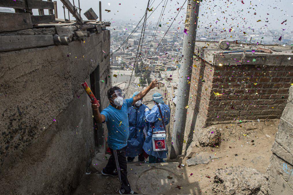 Un hombre celebra después de que los trabajadores de la salud inocularon a Maximiliana Quispe con una dosis de la vacuna Pfizer-BioNTech contra el COVID-19