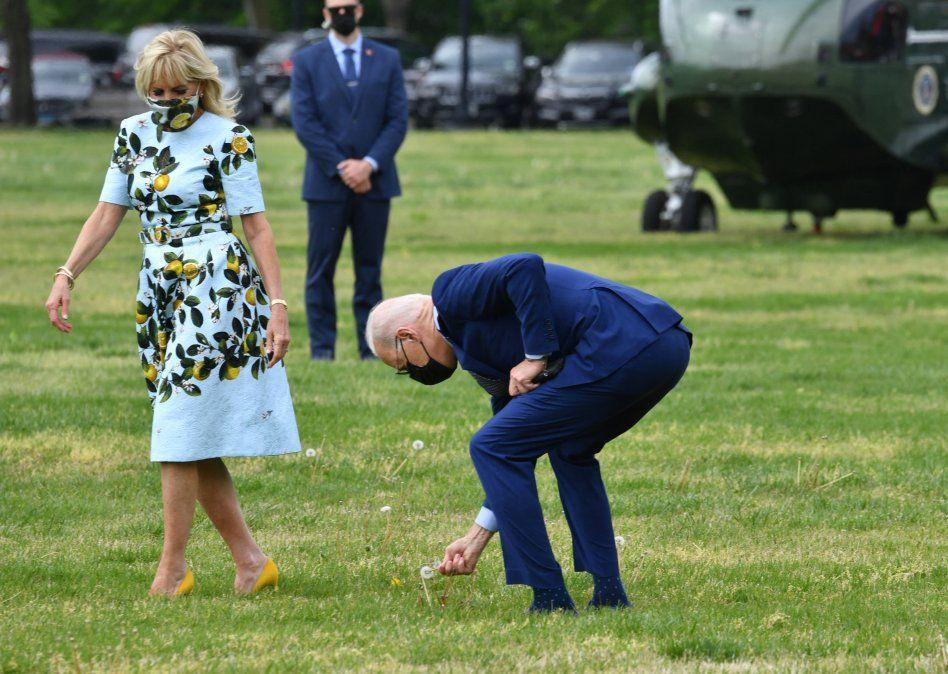 El presidente estadounidense Joe Biden recoge una flor de diente de león para la primera dama Jill Biden