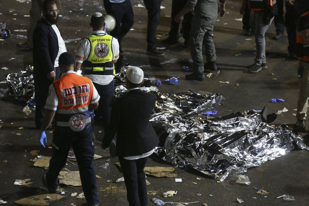 Paramédicos y hombres judíos ultraortodoxos junto a cuerpos cubiertos después de que decenas de personas murieron y otras resultaron heridas después del colapso de una tribuna en Meron