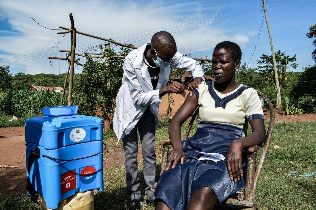 Un trabajador de la salud inyecta la vacuna de Oxford / AstraZeneca a una mujer que visita puerta a puerta en zonas alejadas de los centros de salud en Siaya
