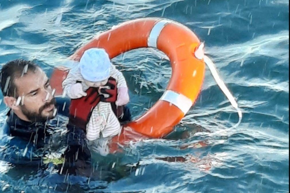 Una imagen publicada por la Guardia Civil española muestra a un miembro sosteniendo a un bebé migrante en el agua frente a la costa del enclave español de Ceuta