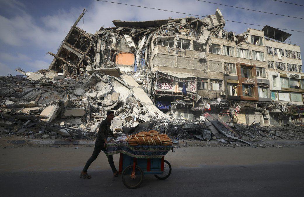 Un palestino pasa frente al edificio destruido de Al-Shuruq en la ciudad de Gaza después de que fuera bombardeado por un ataque aéreo israelí