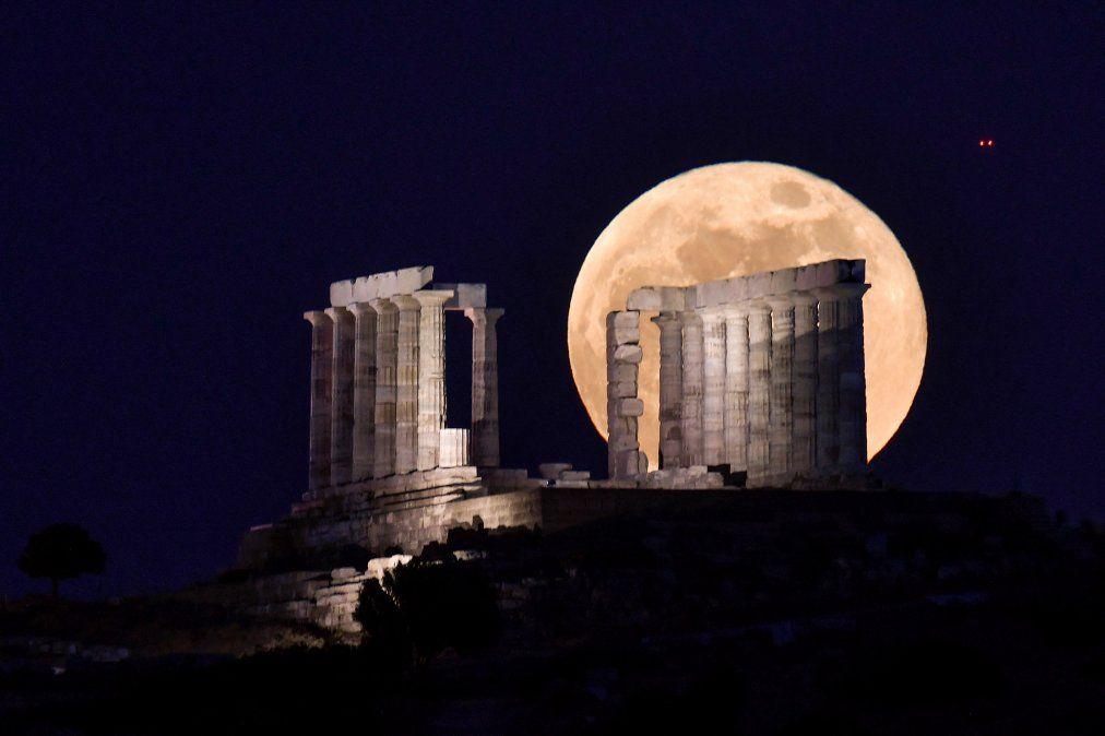 La la luna llena se eleva detrás del 444-440 a. C. Templo de Poseidón (Neptuno) en el cabo Sunión