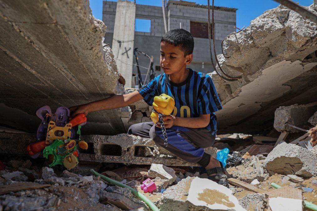 Un niño palestino recupera sus juguetes de los escombros de su casa