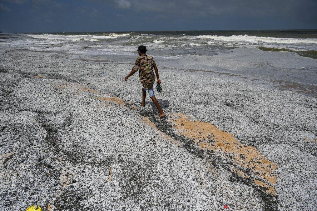 Un hombre camina entre los escombros arrastrados a la costa del buque portacontenedores MV X-Press Pearl