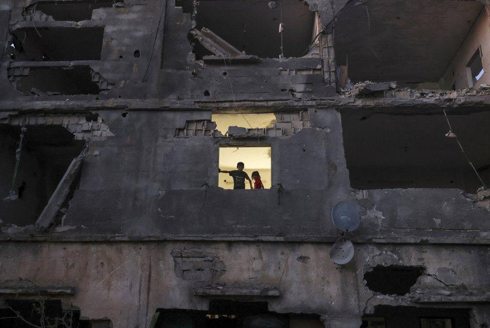 Los niños palestinos se paran en la ventana de su casa en un edificio gravemente dañado durante los recientes ataques israelíes