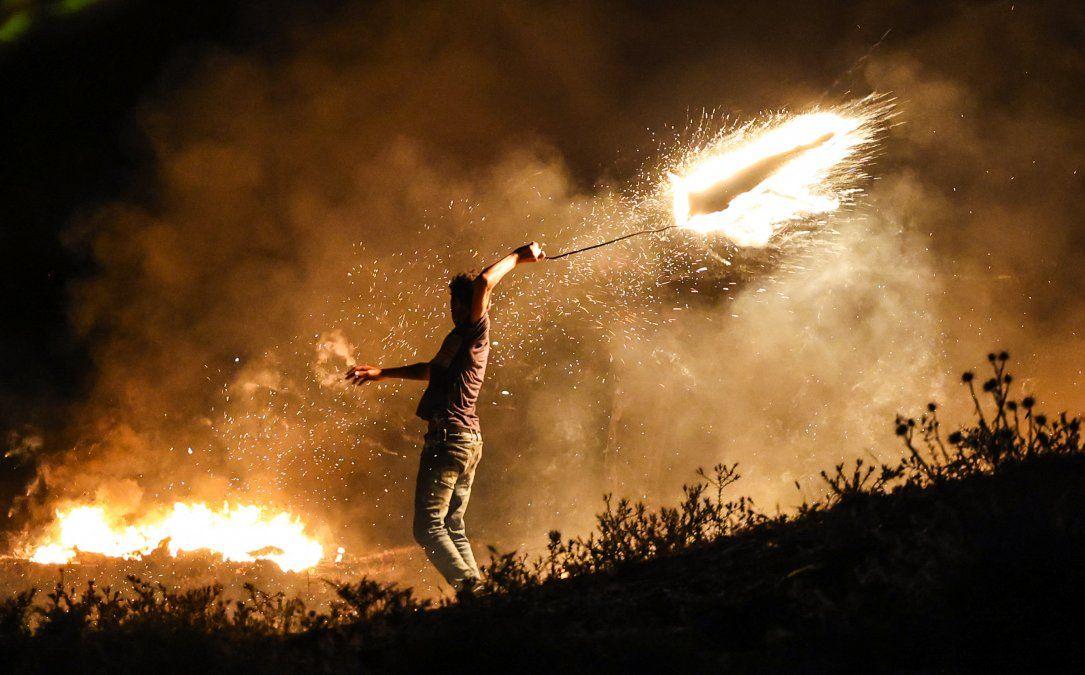 Un manifestante palestino lanza un proyectil ardiente hacia las fuerzas israelíes durante una manifestación al este de la ciudad de Gaza en la frontera con Israel