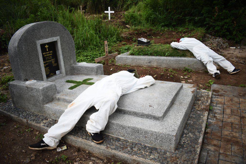 Exhaustos excavadores de tumbas descansan entre los funerales en un cementerio designado para las víctimas de Covid-19 en Bandung