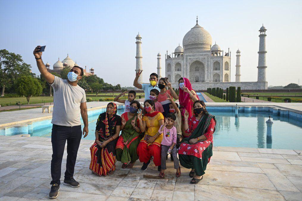 Un grupo de turistas toma fotos en el Taj Mahal después de que reabriera a los visitantes