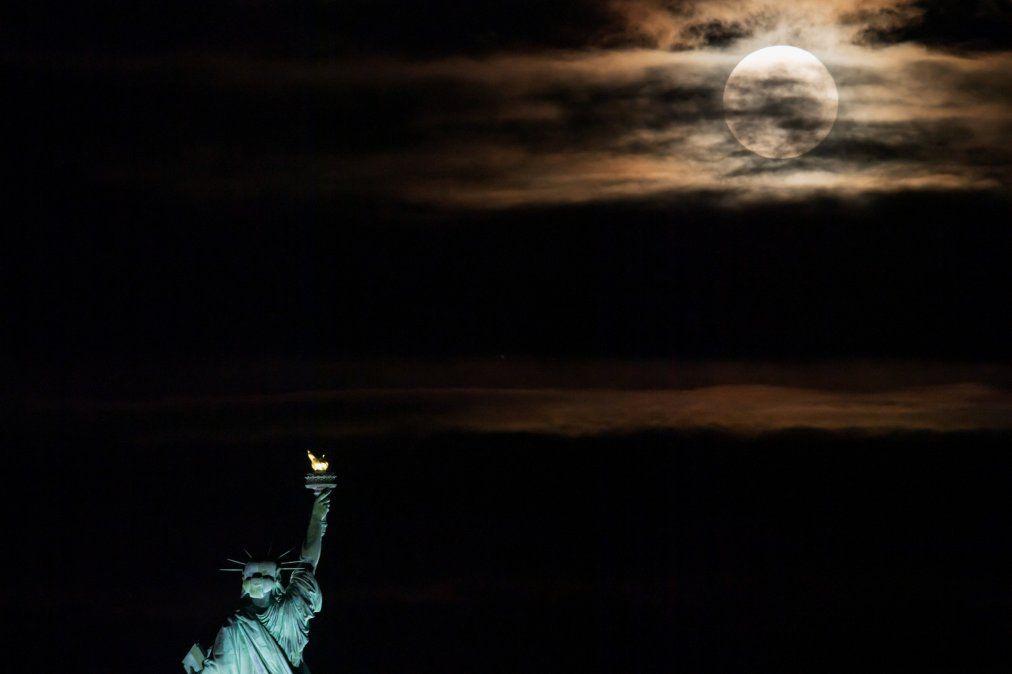 La luna llena se eleva detrás de la Estatua de la Libertad en la ciudad de Nueva York. La luna llena de junio a menudo se conoce como la luna de la fresa porque cae durante la temporada de cosecha de fresas en el noreste de los EE. UU.