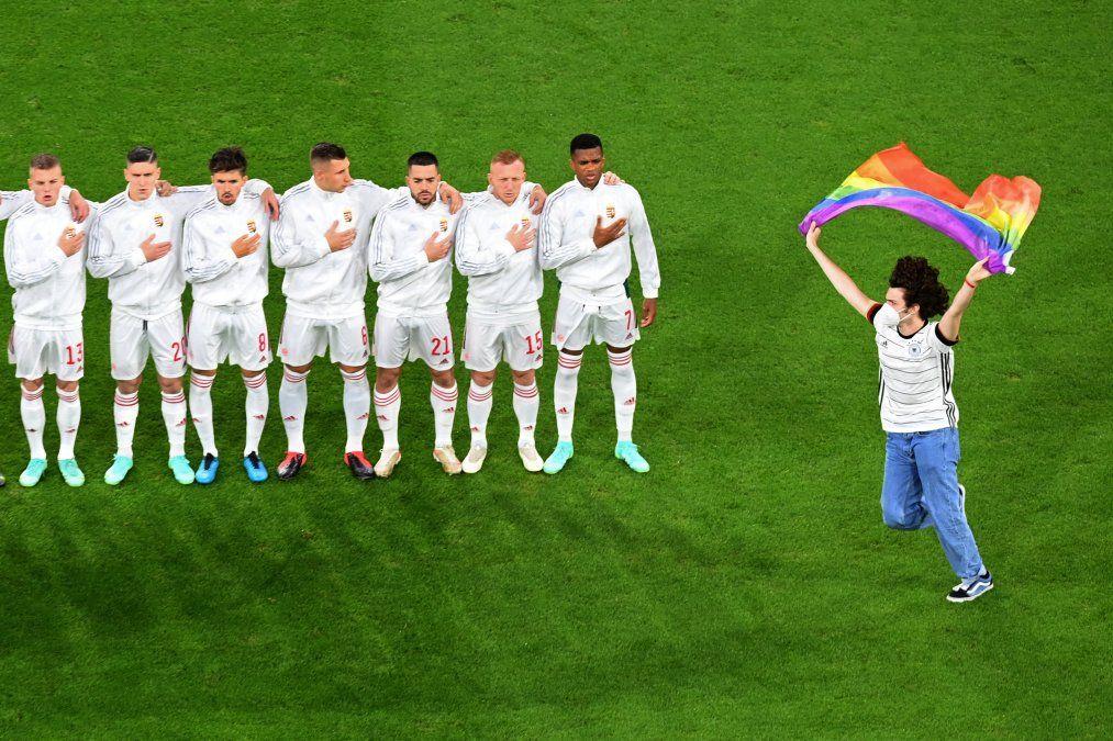 Una persona que agita la bandera del arco iris corre en el campo mientras los jugadores de Hungría se alinean para los himnos nacionales del partido de fútbol del Grupo F de la UEFA EURO 2020 entre Alemania y Hungría.