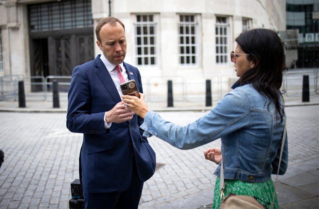 El ministro británico de Salud Matt Hancock mira el teléfono de su asistente Gina Coladangelo (AFP).