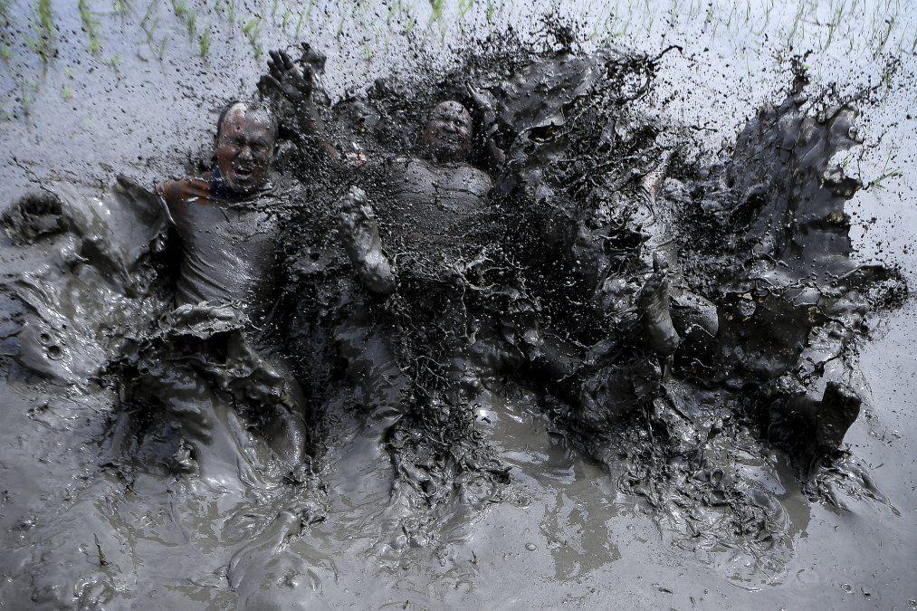 Agricultores cubiertos de barro juegan en un campo durante el Día Nacional del Arroz