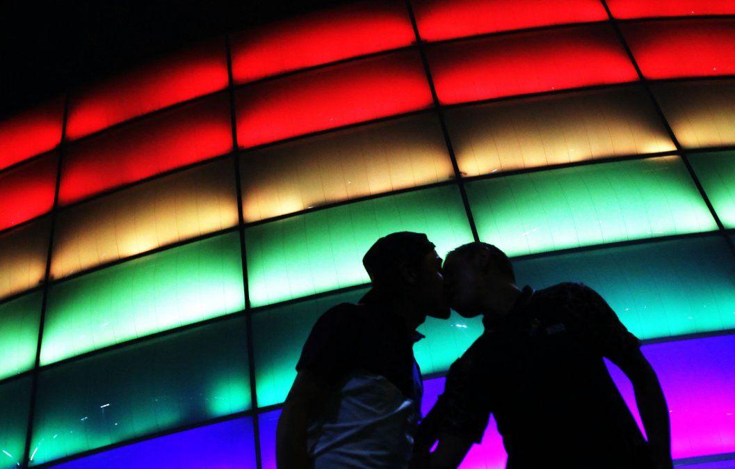 Camilo Barato y Cristian Toquica besan el Movistar Arena coloreado con la bandera del arco iris durante el Día Internacional del Orgullo LGBTIQ en Bogotá