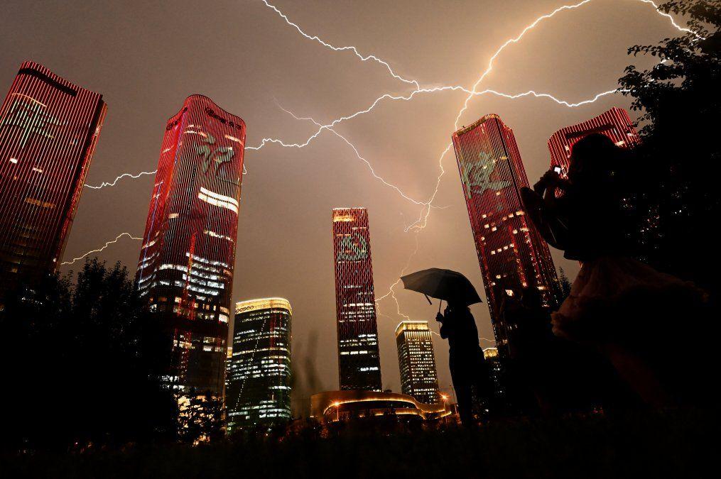 Un rayo cruza el cielo mientras la gente mira los edificios que muestran un espectáculo de luces en la víspera del centenario del Partido Comunista de China en Beijing