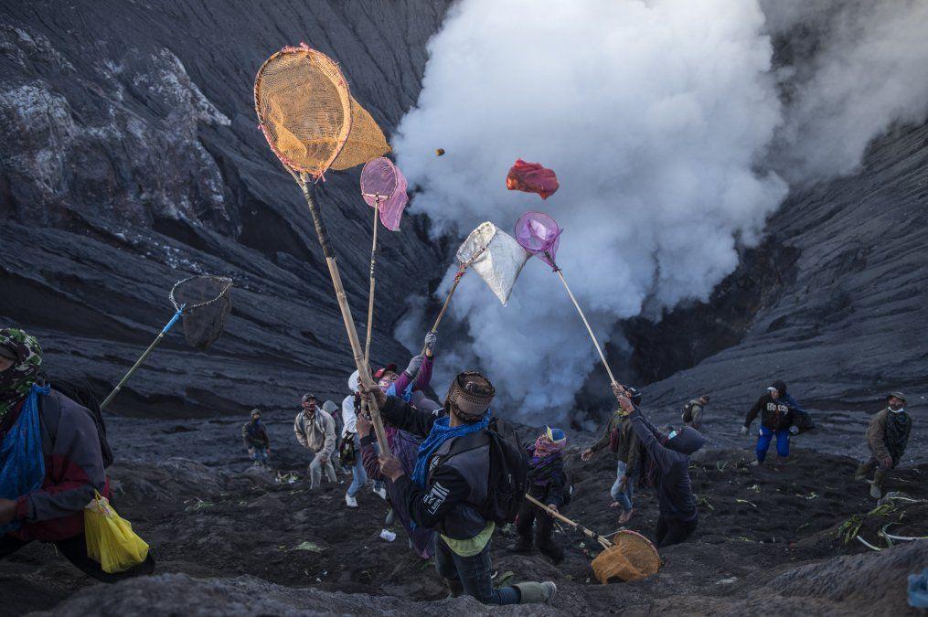 La gente intenta atrapar las ofrendas lanzadas por la gente de la tribu Tengger desde la cima del volcán activo Monte Bromo en Probolinggo