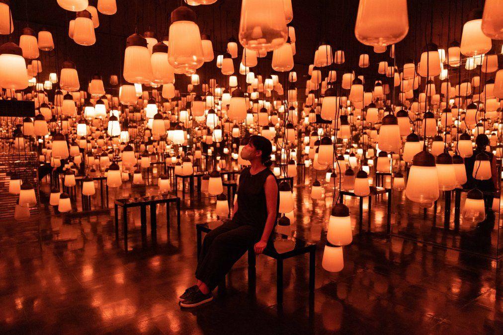 Un miembro del personal se sienta en una instalación digital interactiva Fuego / bosque y espiral de lámparas resonantes en el bosque en Japón