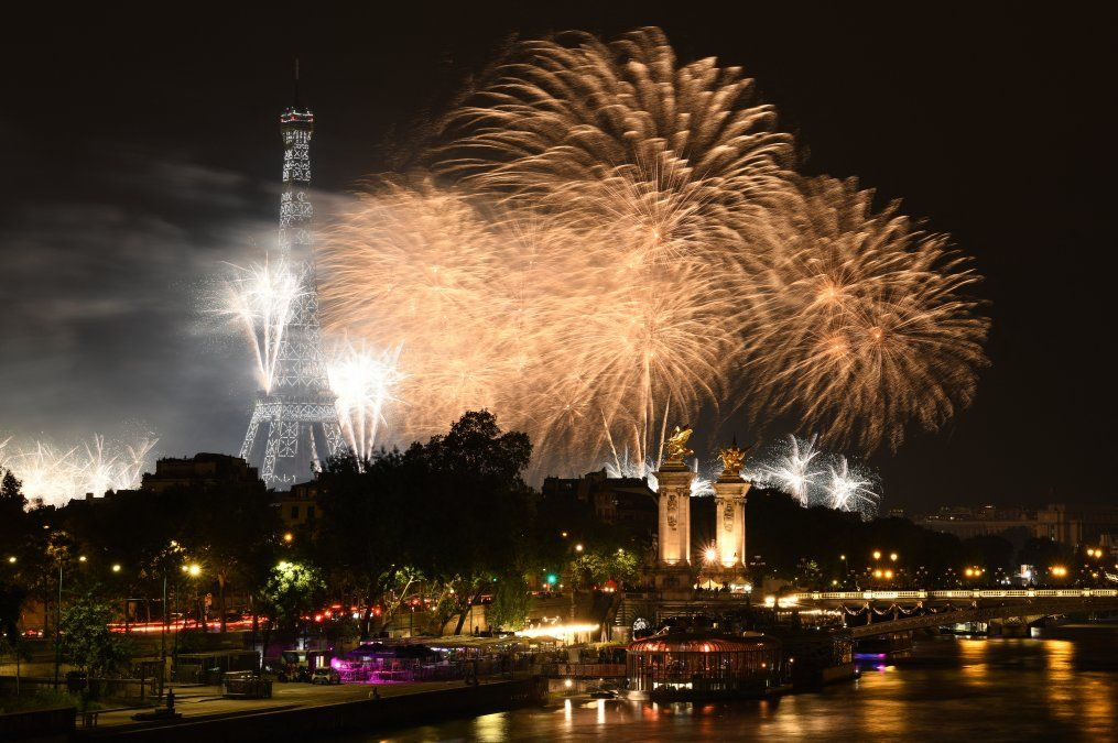 Los fuegos artificiales explotan sobre la Torre Eiffel y el río Sena como parte de las celebraciones anuales del Día de la Bastilla en París