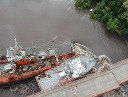 Buzos trabajan para amarrar los buques que chocaron contra el puente de Carmelo
