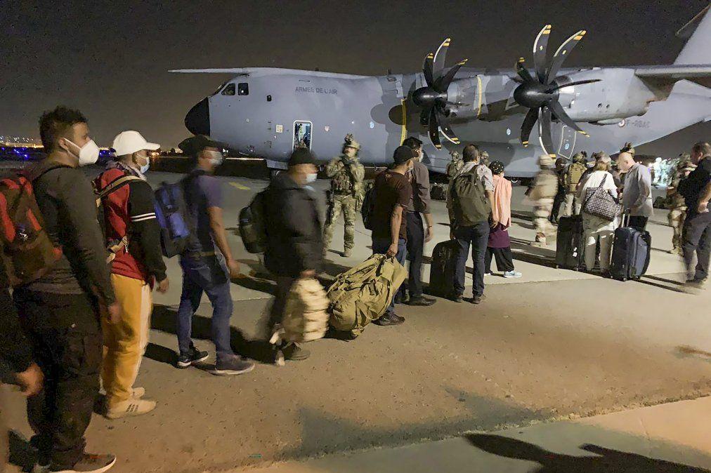 La gente hace fila para abordar un avión de transporte militar francés en el aeropuerto de Kabul el 17 de agosto de 2021
