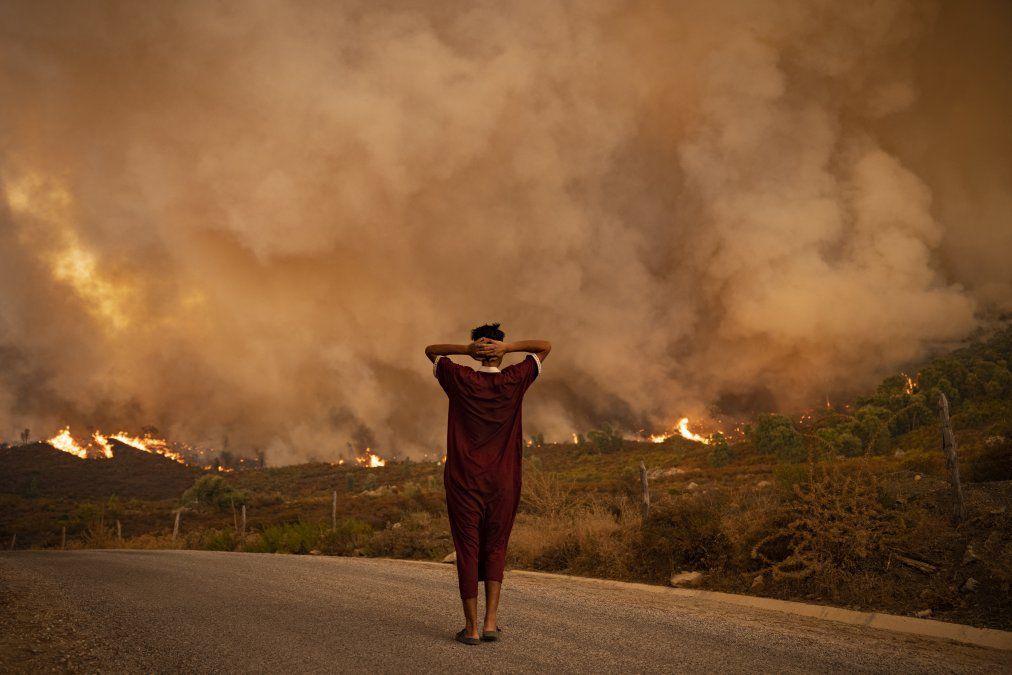 Una mujer observa los incendios forestales que arrasaron un bosque en la región de Chefchaouen en el norte de Marruecos