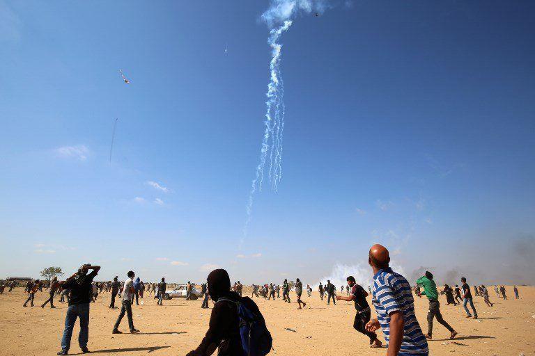 Los manifestantes palestinos observan caer gas lacrimógeno arrojado desde un avión no tripulado israelí el 15 de mayo último.