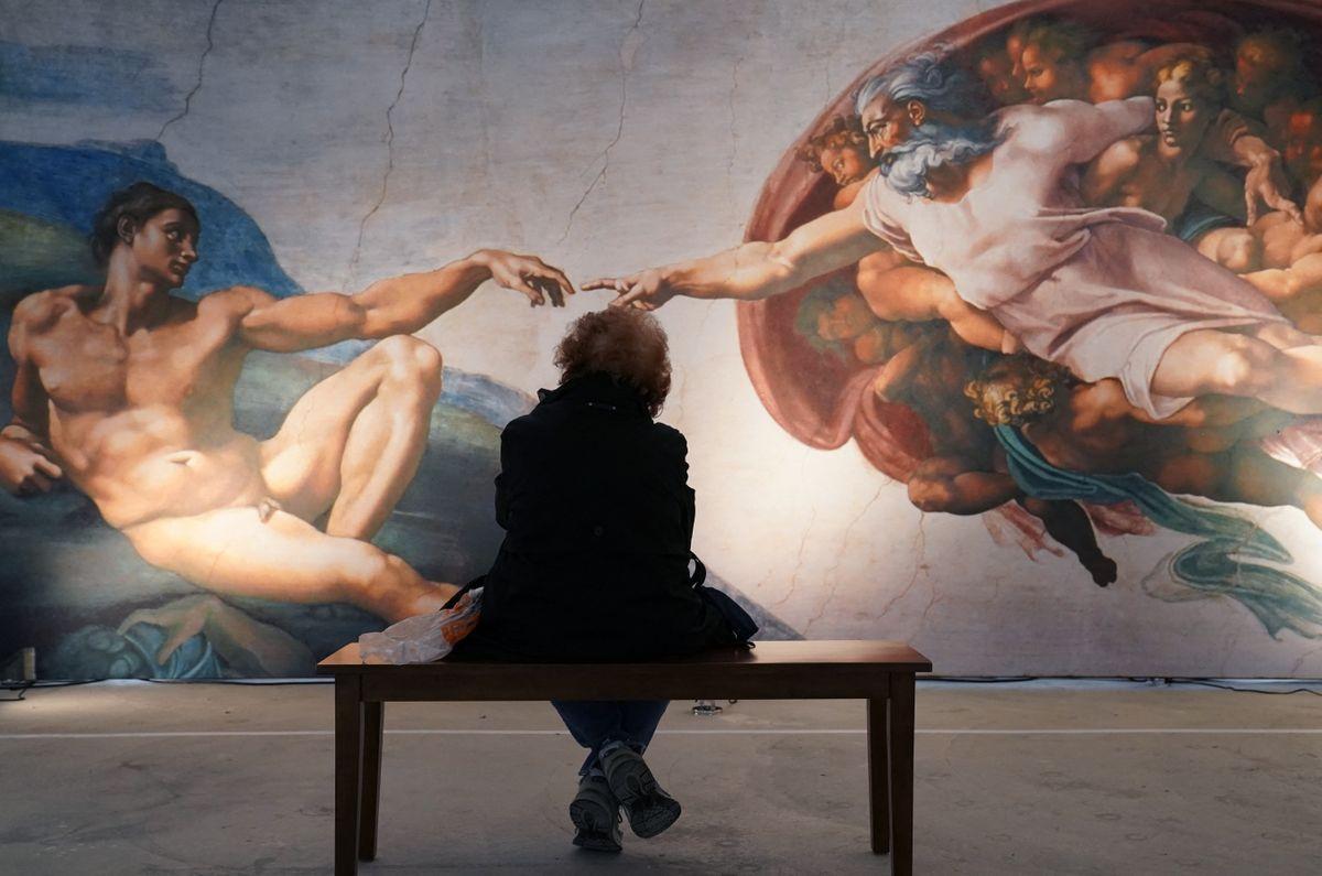 Una mujer mira una de las fotos usando una técnica de impresión para reproducir réplicas a tamaño completo de la Capilla Sixtina del Vaticano