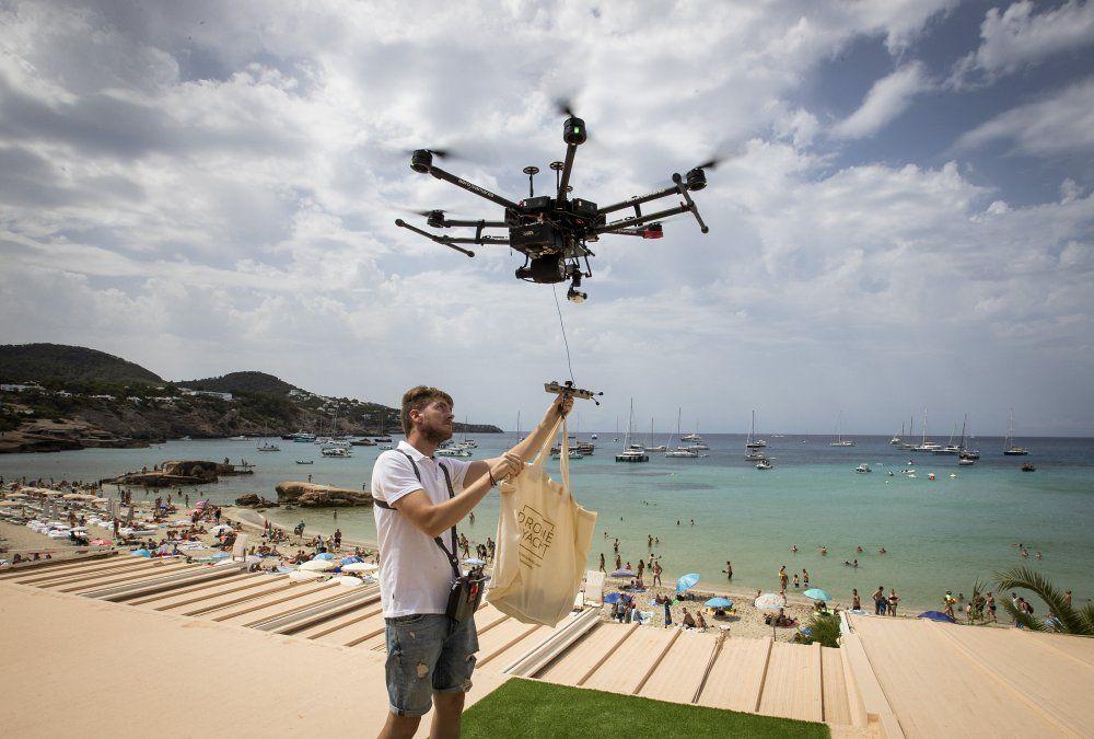 Un piloto de drones amarra una bolsa de comida a un dron en Cala Tadira. Drone to Yacht es un servicio de entrega exclusivo para la entrega de alimentos y bebidas a los yates.