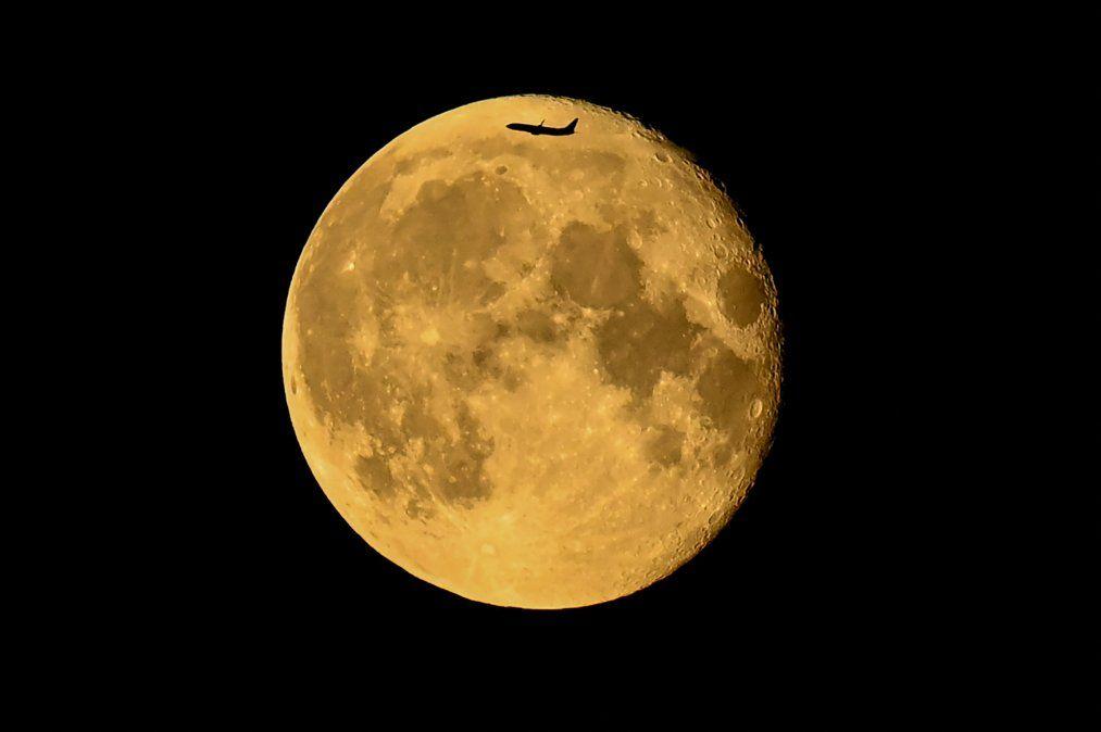 La silueta de unavión delante de la luna menguante en Moscú a última hora del 25de julio.