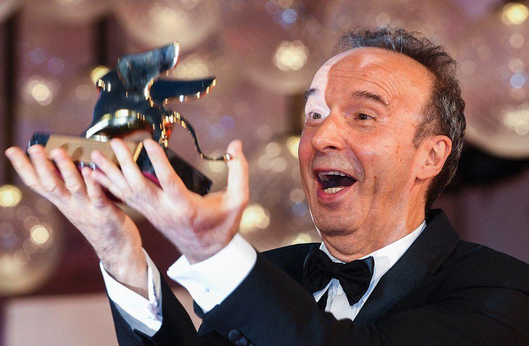 Elactor y director italiano Roberto Benigni lanza su premio León deOro al aire mientras posa para los fotógrafos después de recibir unLeón de Oro por su trayectoria