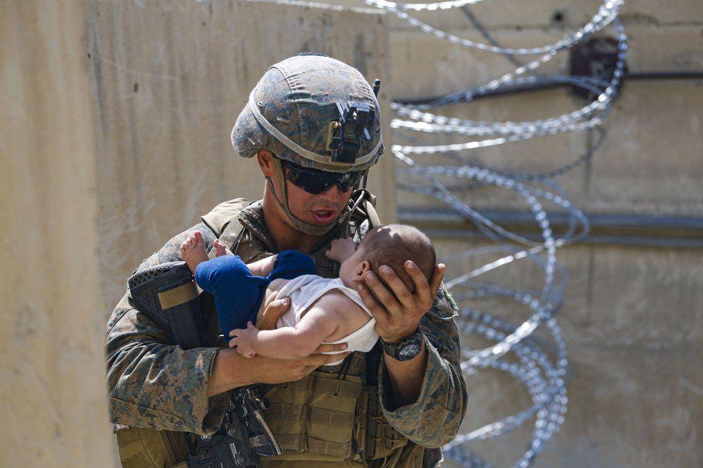 Un infante de marina de los EE. UU. consuela a un bebé mientras esperan a la madre durante una evacuación en el Aeropuerto Internacional Hamid Karzai