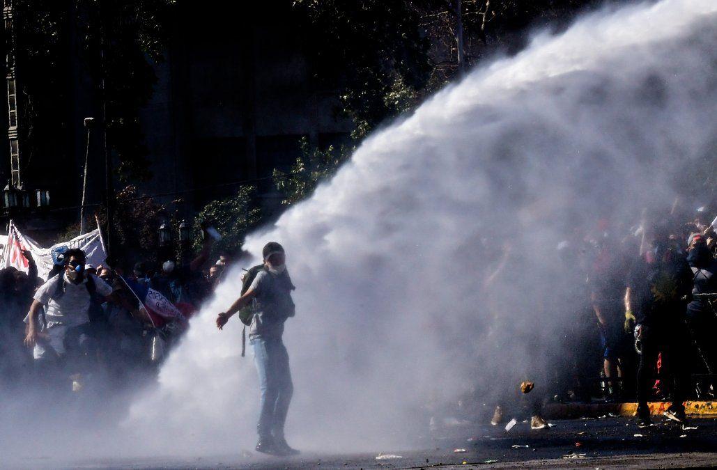 Manifestantes son rociados con agua por la Policía militarizada chilena.